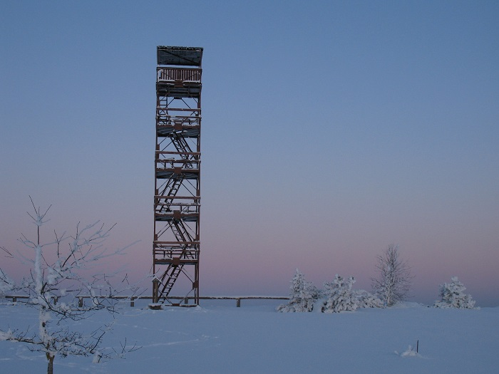 a observation tower with 5 stairs in a snowy landscape with blue-pink colour sky and ground as the sun is setting