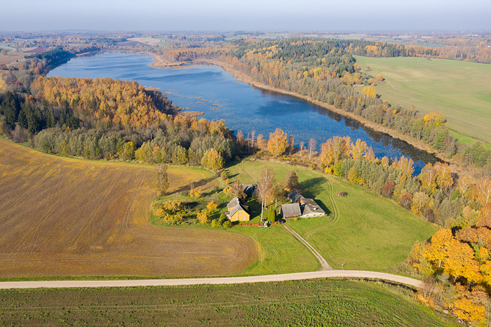 a aeral view with a farmhouse, forest, fields and lake Pikkjärv in autumn